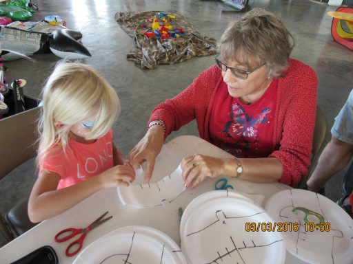 Liz Basser helps a young visitor with a foam plate gliders.