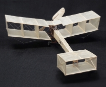 "Here is Emil's peanut size model of the Santos Dumont 14. wingsan is 13"". In 1906 Santos-Dumont designed the first French airplane, a lightweight box-kite plane 14-bis, built for him by the Voisin brothers. The 14-bis  pioneered wheeled landing gear, and in 1906, became the first airplane to fly in public (leading many to believe that Santos-Dumont had achieved the first successful airplane flight)."